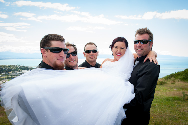 wedding photo groomsmen groom bridal party nelson nz groomsmen lift bride