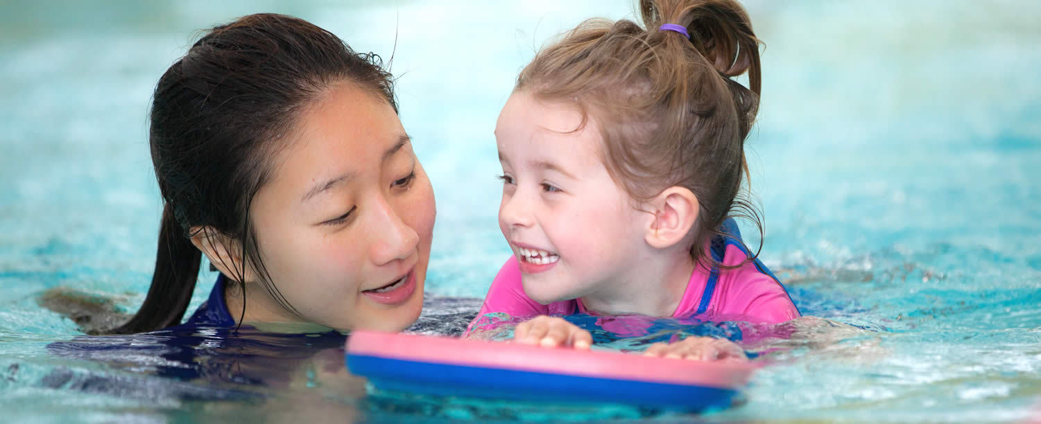 Girl swimming with instructor