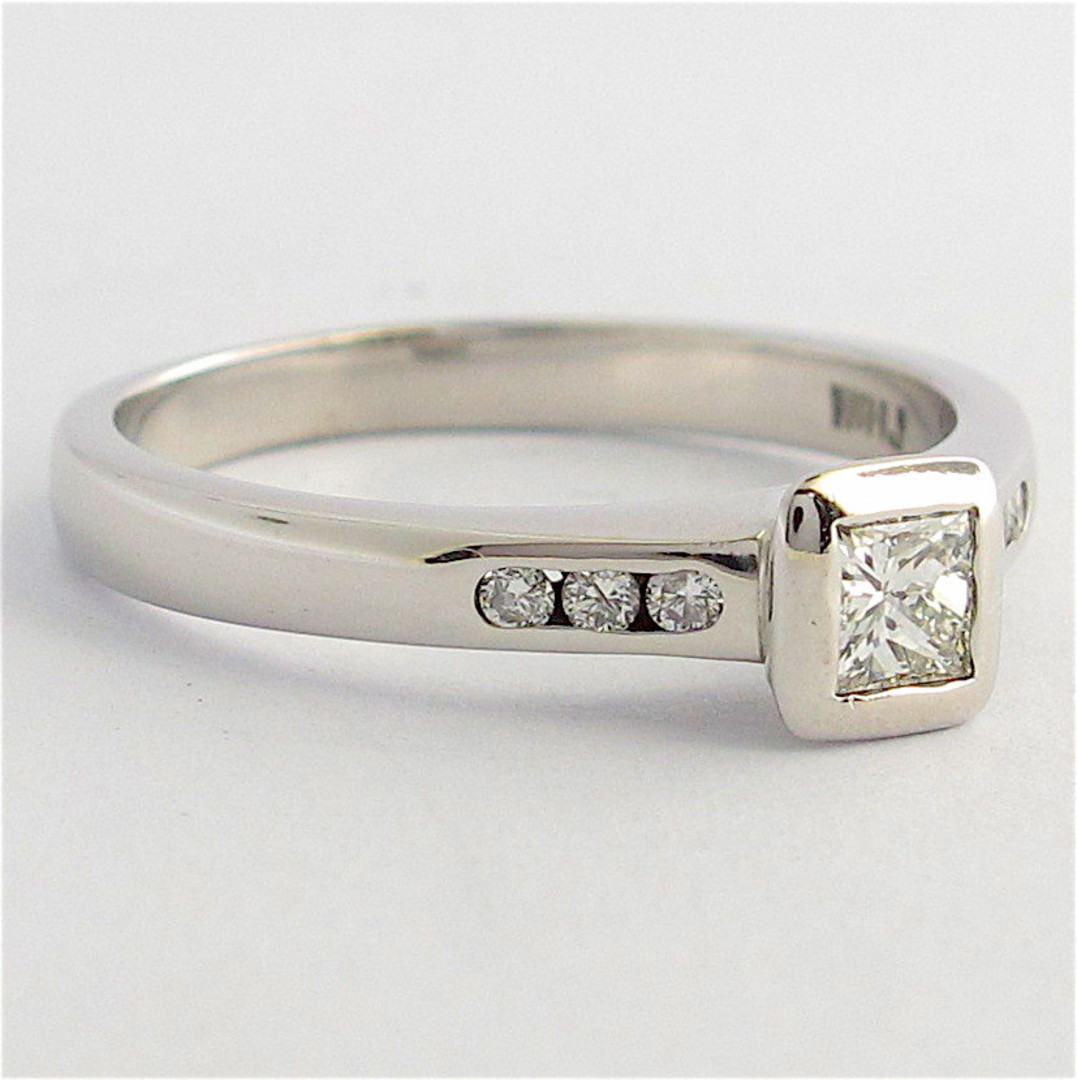 18ct white gold diamond solitaire ring with channel set diamond shoulder detail image 1