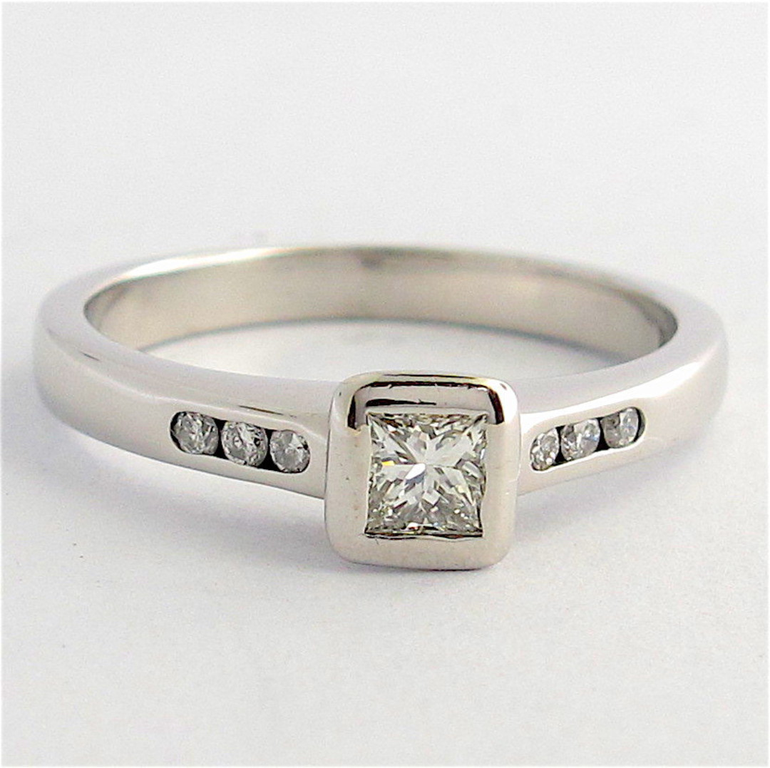 18ct white gold diamond solitaire ring with channel set diamond shoulder detail image 0