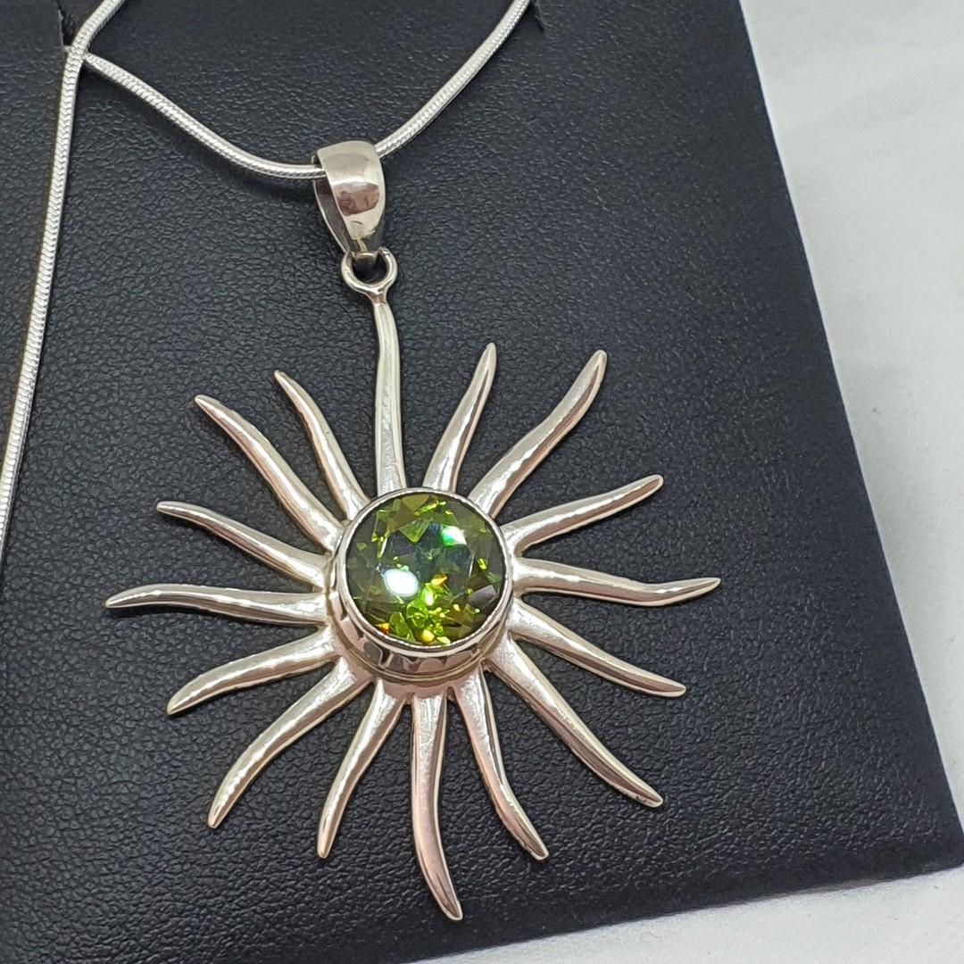 Silver star pendant with sparkling green gemstone image 1