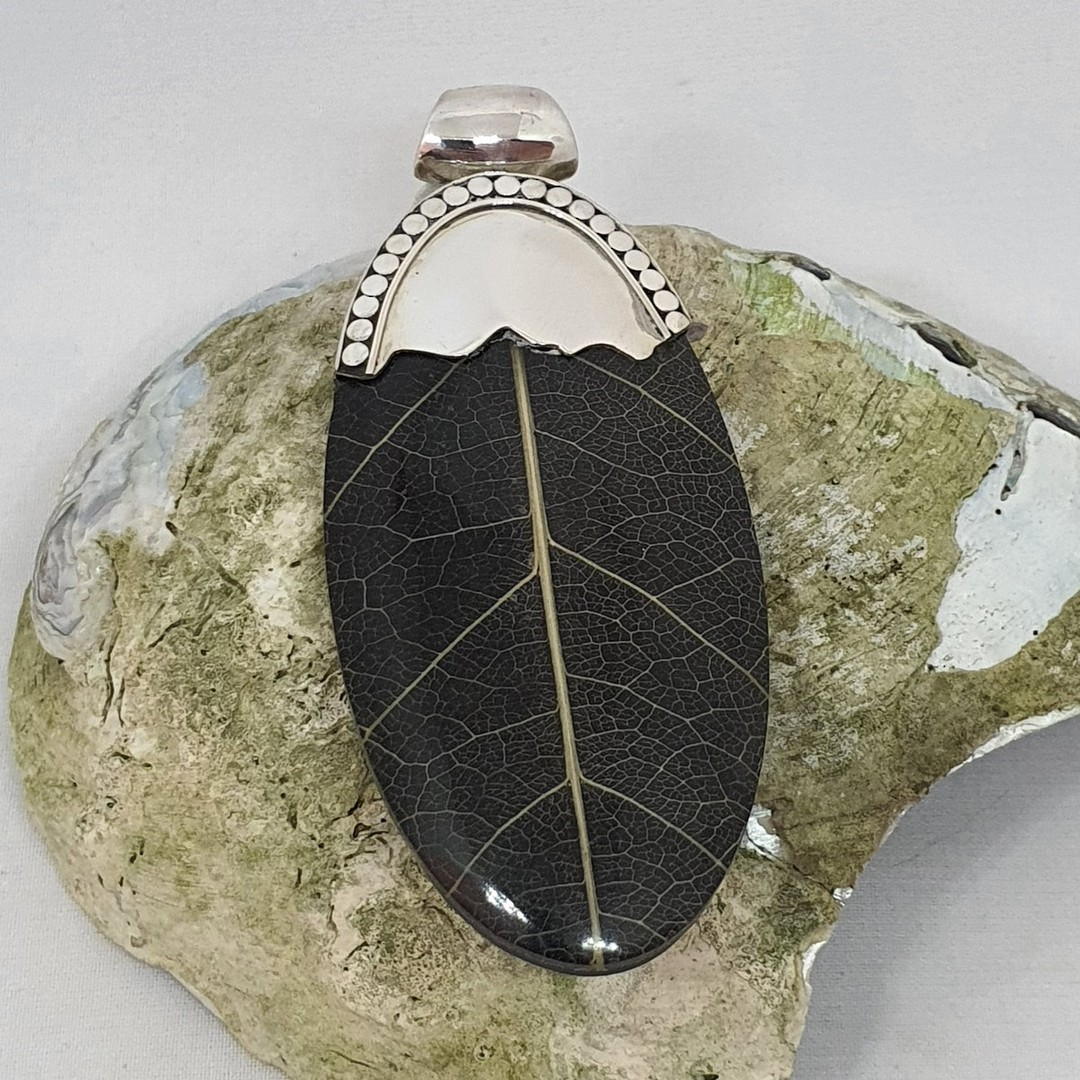 Black skeleton leaf pendant with silver detailing image 1