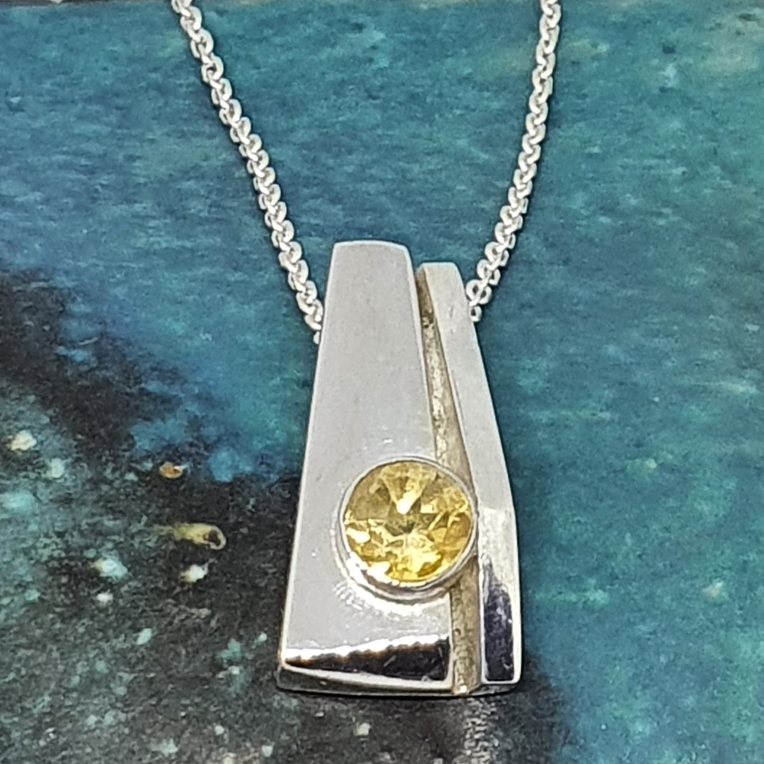 Silver pendant with a golden gemstone image 0