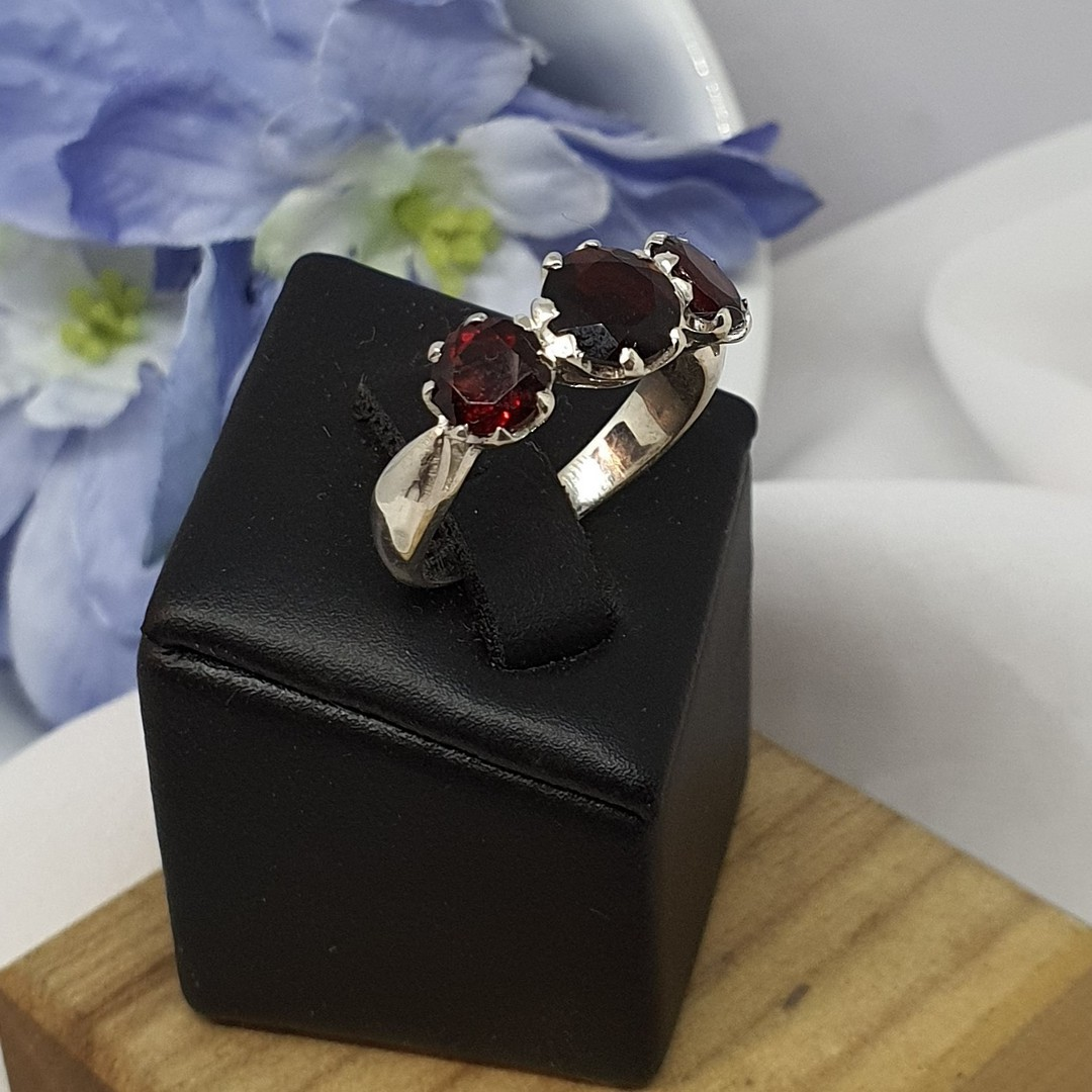 Silver ring with three sparkling red gemstones image 2