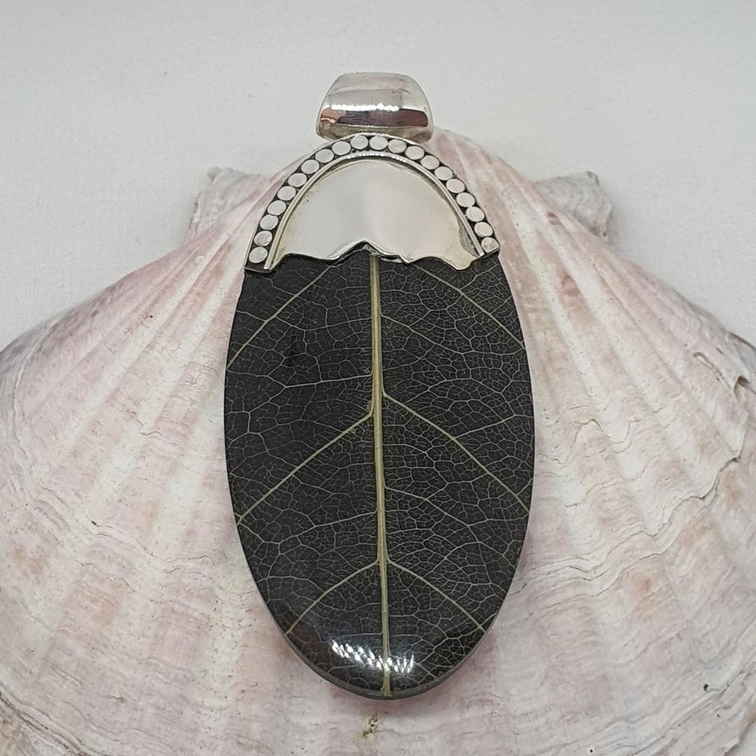 Black skeleton leaf pendant with silver detailing image 0