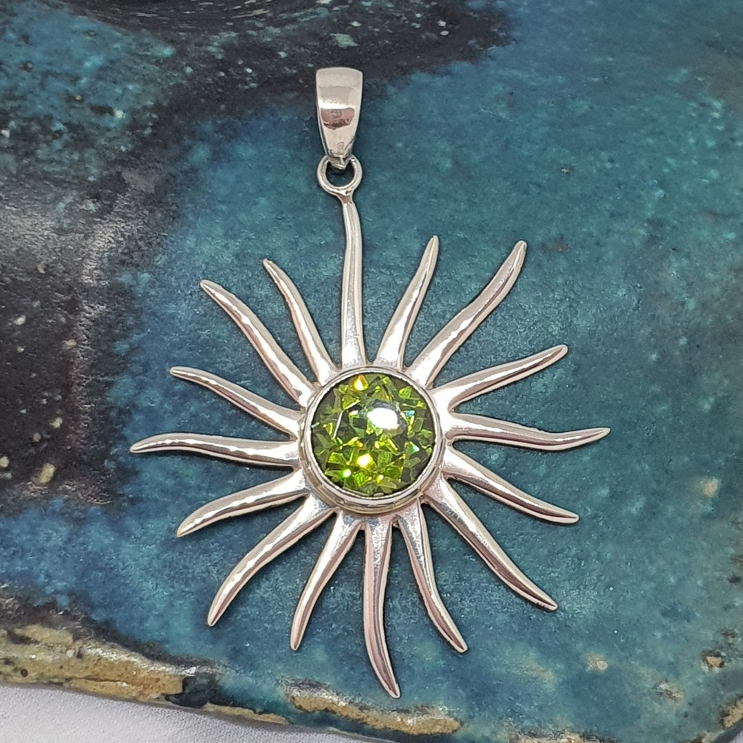Silver star pendant with sparkling green gemstone image 0