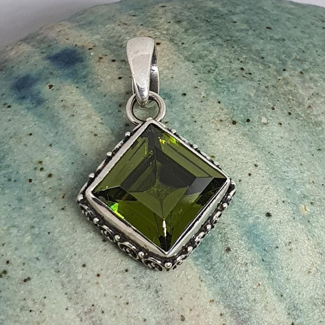 Silver peridot pendant with filigree frame image 0