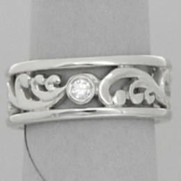 R279 White Gold wedder with a fine carved koru centre, diamond set .