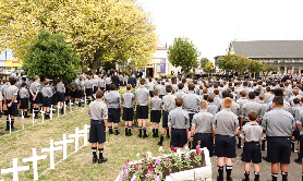 Boys stand by corridor of crosses