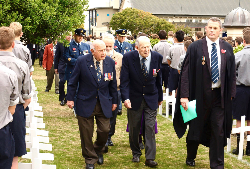 Guests and Veterans walk between the crosses