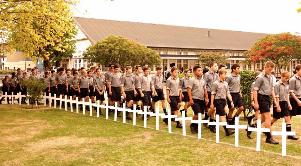 Boys walk between the crosses of Fallen Old Boys