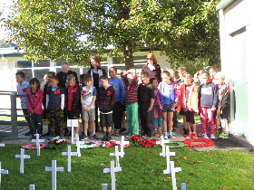 Children assembled by their Field of crosses