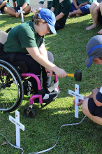 Girl hammering in a cross from her wheelchair