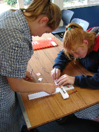 Students applying the name label to a cross