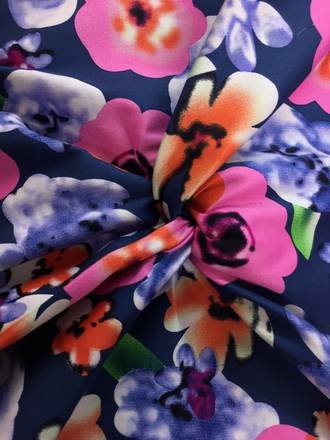 Cotton Spandex pixelated pink flowers on mid blue ground
