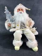 40CMH SITTING SANTA IN IVORY HOLDING GIFT BOXES AND A TREE