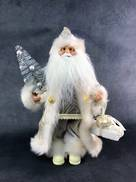 30CMH STANDING SANTA IN IVORY HOLDING GIFT BOXES AND A TREE