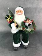 40CMH SITTING SANTA IN GREEN WHITE HOLDING A WREATH AND GIFT