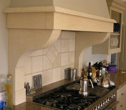 Kitchen range hood hand carved in Oamaru Limestone with aged patina