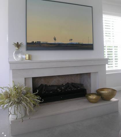 Linear styled fire surround with Raised hearth carved in Portuguese limestone