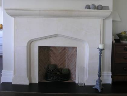 Victorian Gothic revival fire surround carved in Oamaru limestone with lightly aged patina
