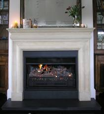 Bolection style fireplace mantle carved in Oamaru Limestone with aged patina