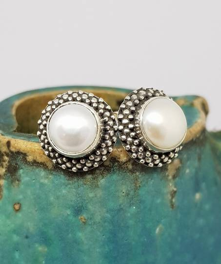 White pearl stud earrings with decorated setting