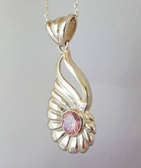 Curved silver shell pendant with pink gemstone