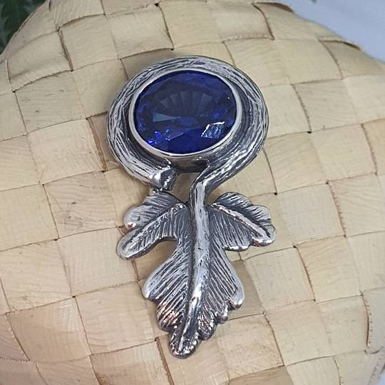 Large blue gemstone pendant with silver leaf design