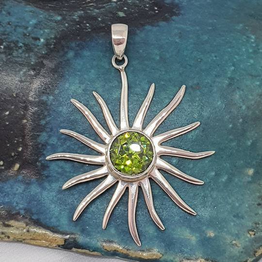 Silver star pendant with sparkling green gemstone