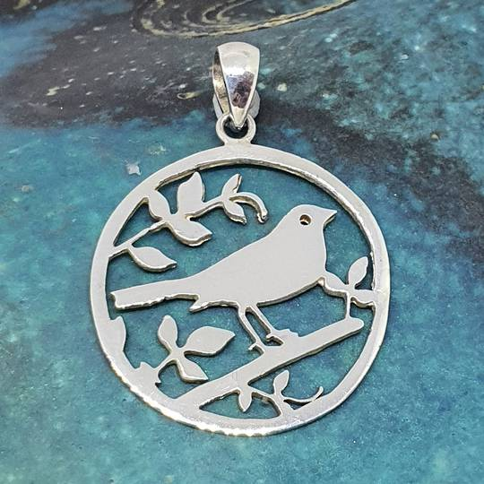 Silver pendant with a bird in a tree