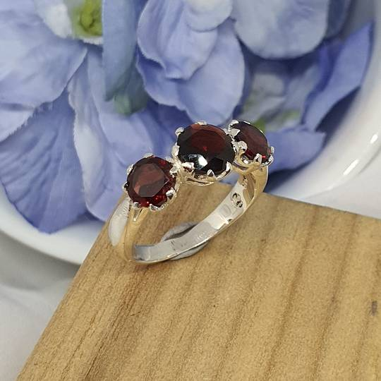 Silver ring with three sparkling red gemstones