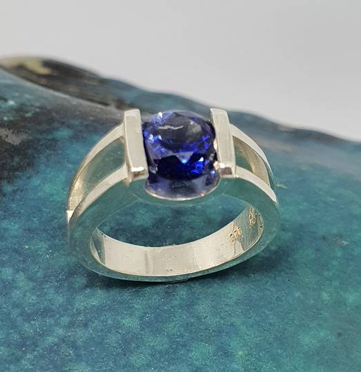 Open sides, sterling silver ring with deep blue gemstone