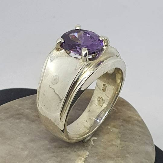 Wide silver band ring with purple gemstone