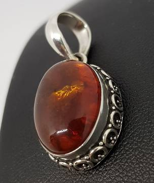 Oval amber pendant with silver filigree frame