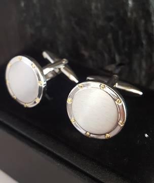 Round silver tone cufflinks with gold flecks